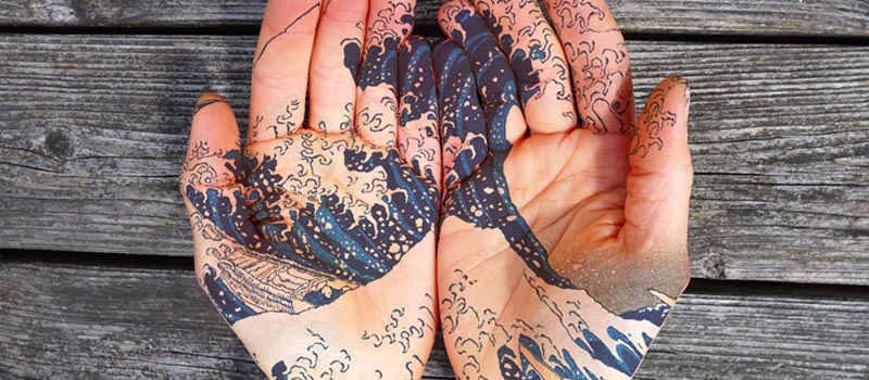 Image by Toni Davey of Tattooed hands featuring Hokusai's iconic woodcut, 'The Great Wave of Kanagawa'.