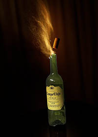 photograph of a bottle of wine with the cork exploding from the mouth