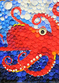 Red and orange octopus swimming in the ocean, made from plastic bottle tops.