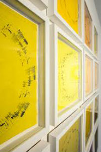 Yellow artwork in frames on. There are black circular ripples on each yellow background.