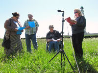4 people in a field with a microphone and scripts
