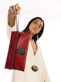 A lady holding a red leather purse in the air.