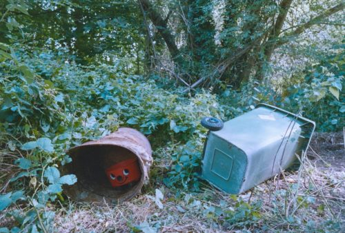 Photograph of derelict Saxonvale site with discarded objects including a wheelie bin and a Henry Hoover vacuum.
