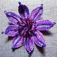Embroidered purple flower with red bead stamen.
