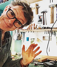 Photograph of Liz Huband, waving from her studio. A range of tools are on the wall behind.