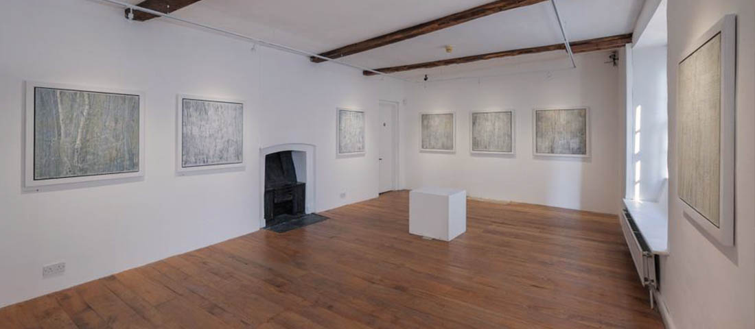 The Long Gallery with minimalist abstract paintings on the wall. The floor is wooden and the walls are white.