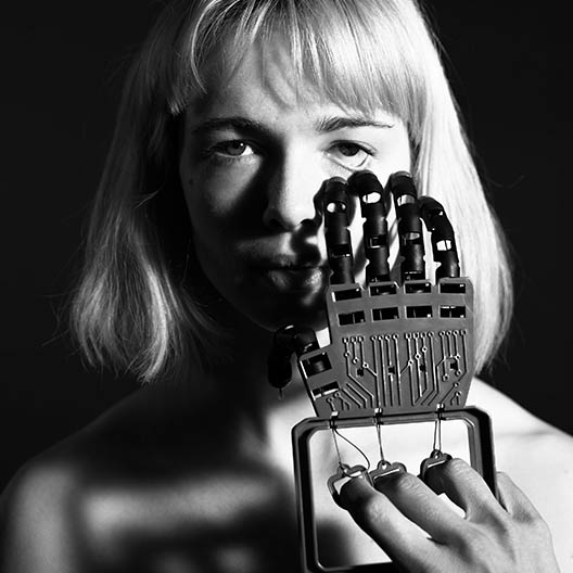 black and white photograph showing a woman holding a mechanical hand to her face